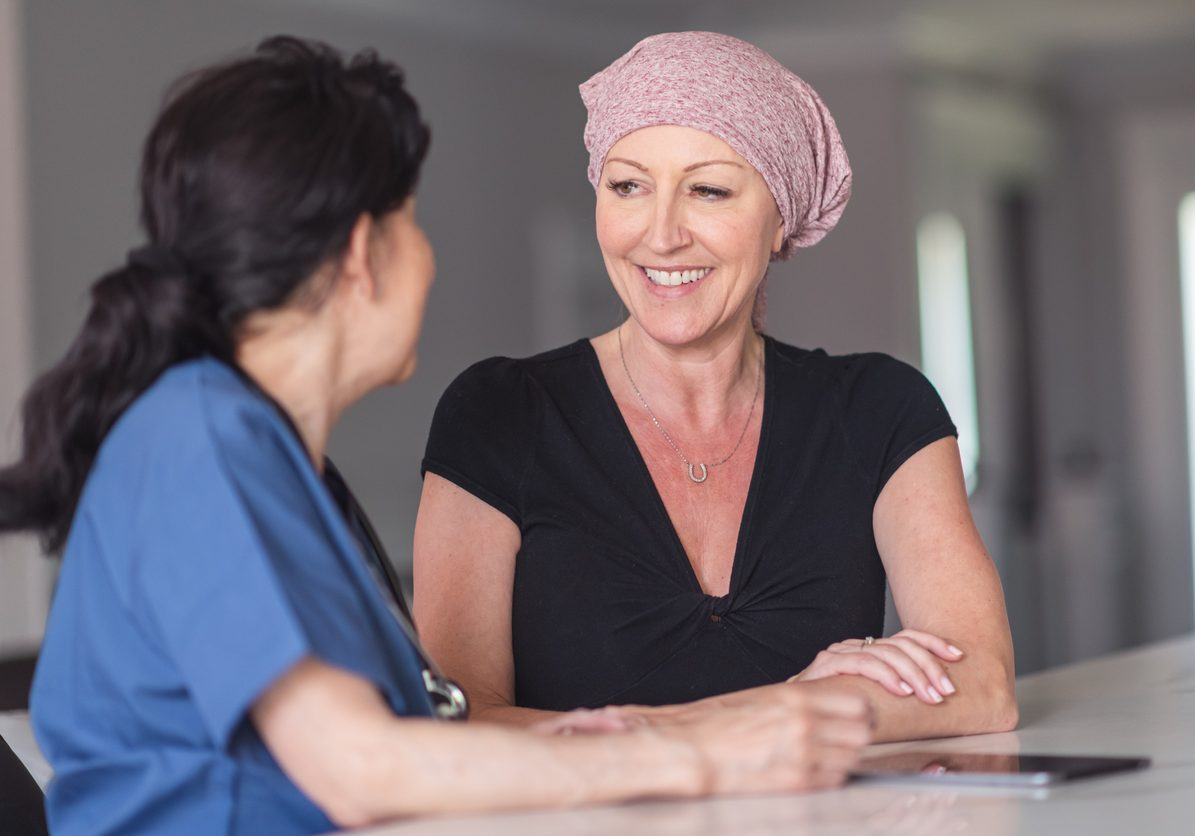 An caucasian woman with cancer is meeting with her female. They are seated next to each other in a clinic. The doctor is showing the patient test results on an electronic wireless tablet. The patient is asking the doctor questions about her treatment and recent test results. She is smiling because her doctor has given her good news.